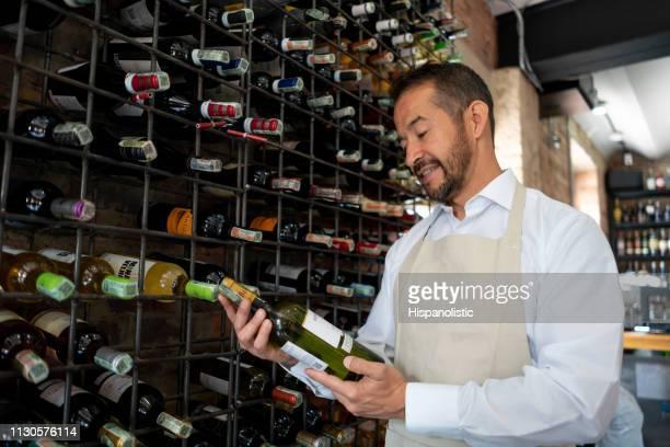 それを見て白いワインボトルを持っているラテンアメリカのウェイター - 地下貯蔵室 ストックフォトと画像