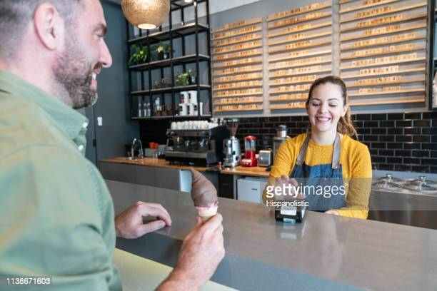 latin american waitress getting the credit card reader ready so customer can pay his ice cream both smiling - ice cream parlour stock pictures, royalty-free photos & images