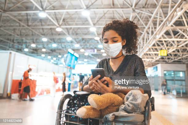 latin american wearing protective mask in airport - coronavirus airport stock pictures, royalty-free photos & images