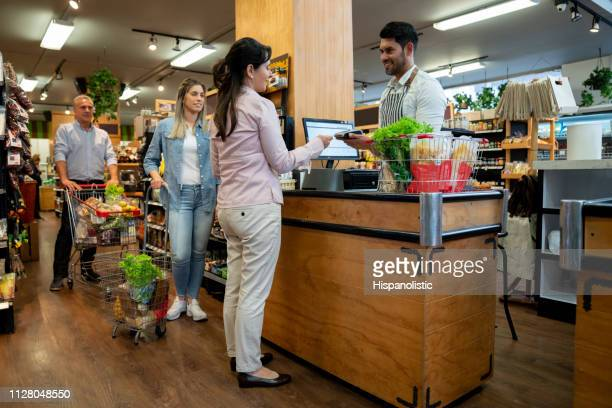 latin american woman paying for groceries with debit card and other customers waiting in line - in a row stock pictures, royalty-free photos & images