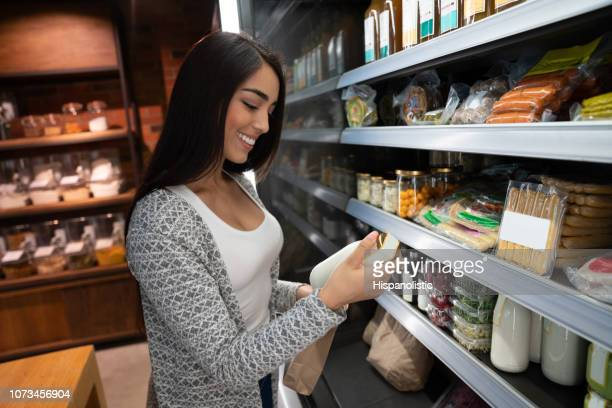 latin american woman reading the label from a refrigerated product at a supermarket smiling - hispanolistic stock photos and pictures