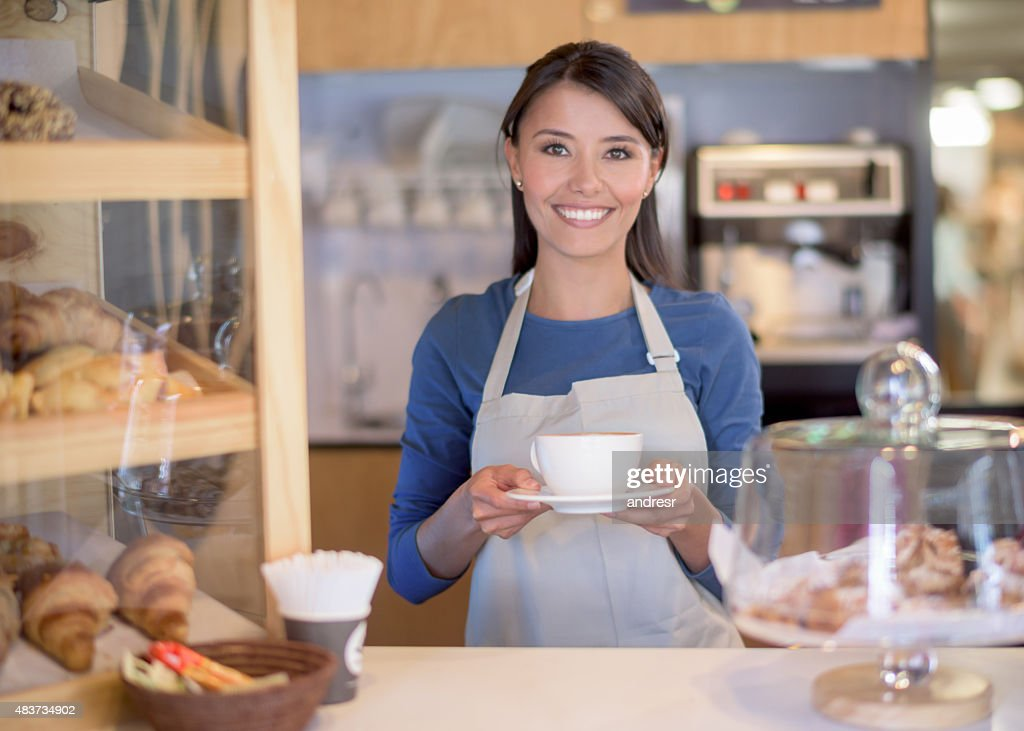 Latin American woman serving coffee at a cafe : Stock Photo