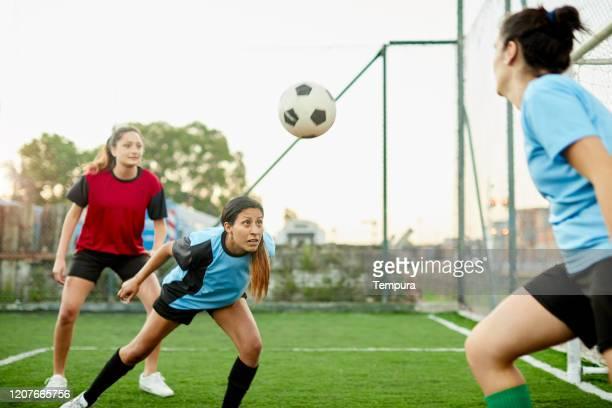 una mujer latinoamericana teniendo un tiro en la cabeza en un partido de fútbol. - liga de fútbol fotografías e imágenes de stock