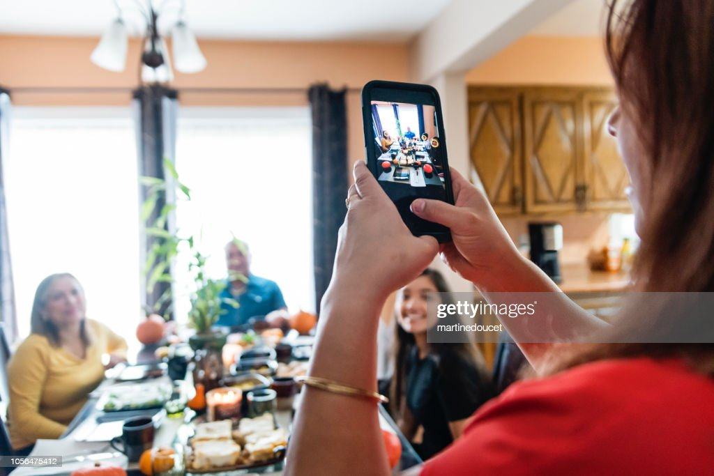 Latin American woman taking photo of the family at meal time. : Stock Photo