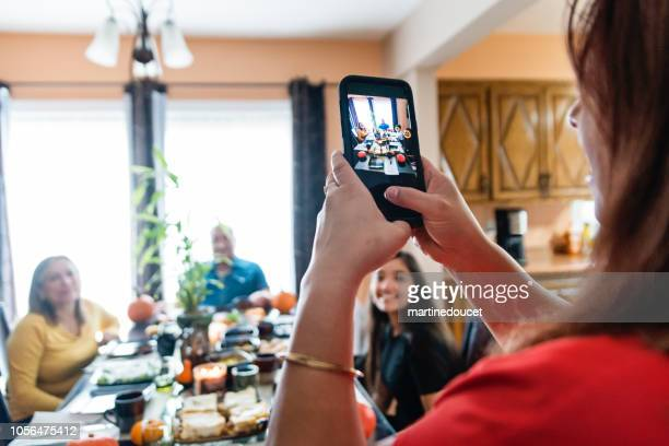 Latin American woman taking photo of the family at meal time.