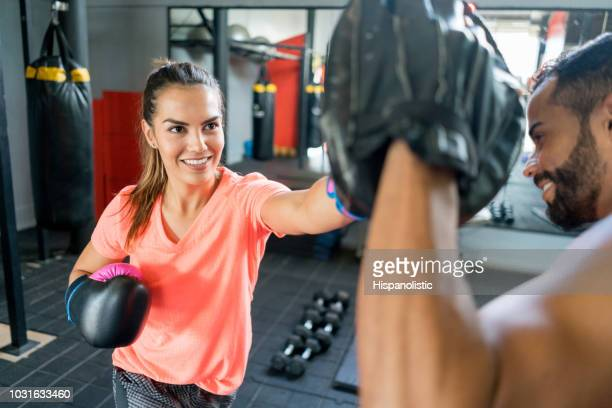 latin american woman training kickboxing with her male coach - kickboxing stock pictures, royalty-free photos & images