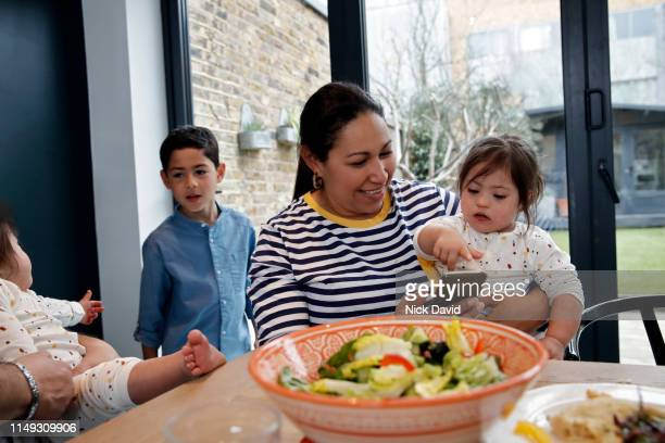 Latin American woman using mobile phone in kitchen with daughter on lap