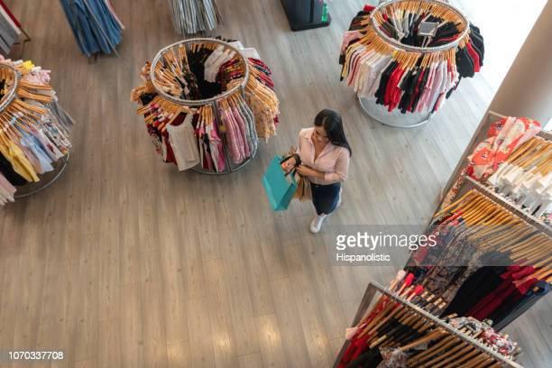 衣料品店でショッピング バッグを押しながら歩いているラテン アメリカ女性 - 百貨店 ストックフォトと画像