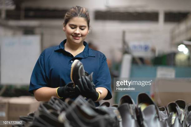 Latin american woman working at a shoe factory checking the leather shoes while smiling