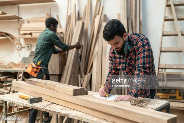 latin american young carpenter working on a design while black man is reaching for wood planks - carpenter stock pictures, royalty-free photos & images