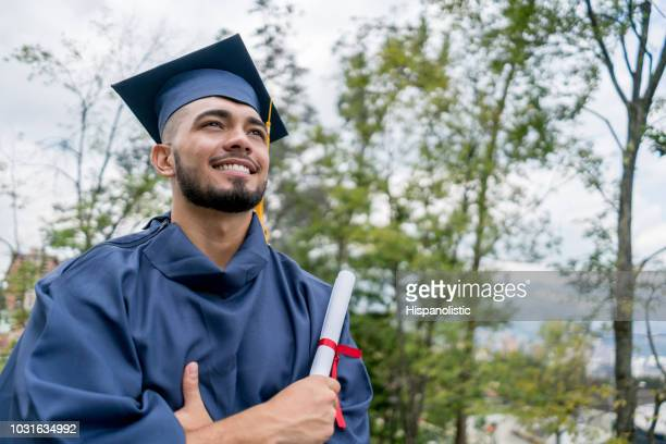 latin american young man very happy after receiving his diploma looking away with arms crossed - graduation stock pictures, royalty-free photos & images