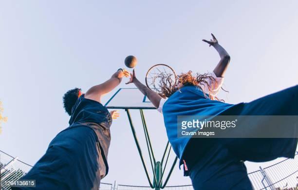 latin and african women play basketball - atleta papel social fotografías e imágenes de stock
