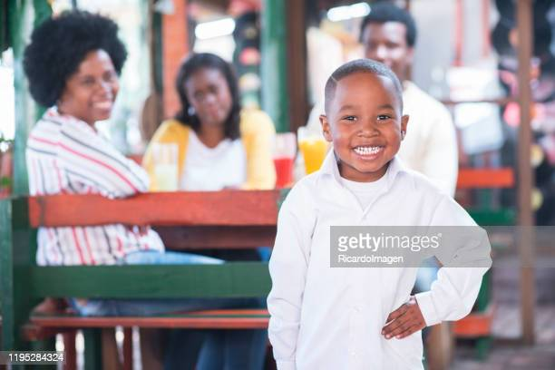 latin boy of approximately 7 years of brown skin white shirt shows a beautiful smile to the camera while we look back at his grandmother mom and dad sitting at a wooden table of beautiful typical city restaurant - 25 29 years stock pictures, royalty-free photos & images