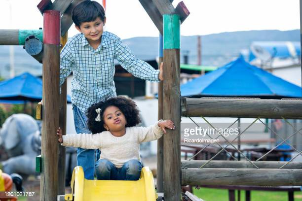 latin boy with brown hair and approximate age of 8 years is standing in a wooden house waiting for his turn to slide down the slide and in front of the girl with afro hair and brown skin of 4 years ready to slide - 4 5 years stock pictures, royalty-free photos & images