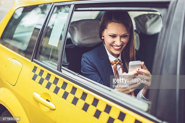 Latin businesswoman text messaging in a taxi cab