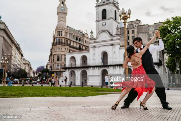 latin couple dancing tango on town square - argentina stock pictures, royalty-free photos & images