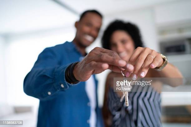latin couple holding the keys of their new house - computer key stock pictures, royalty-free photos & images