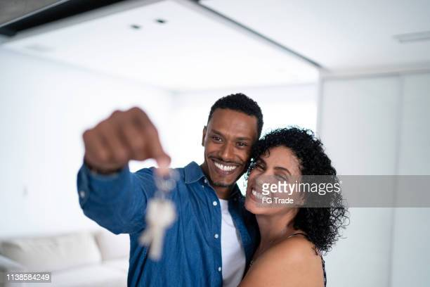latin couple holding the keys of their new house portrait - computer key stock pictures, royalty-free photos & images