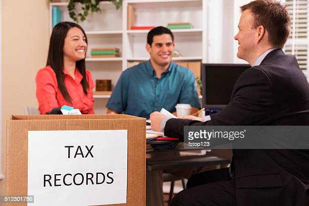Latin couple reviews income tax documents with accountant. Office.