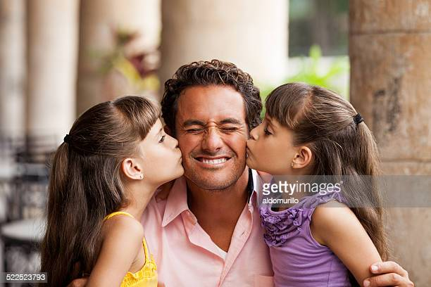 Latin daughters kissing father
