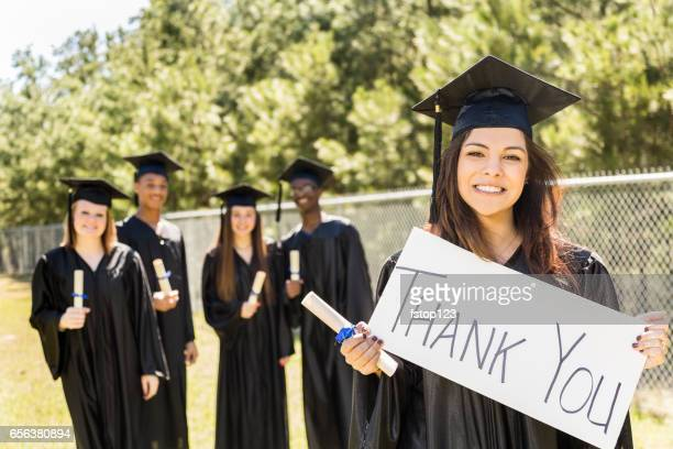 Latin descent college, high school student holds 'Thanks, Dad' sign at graduation.