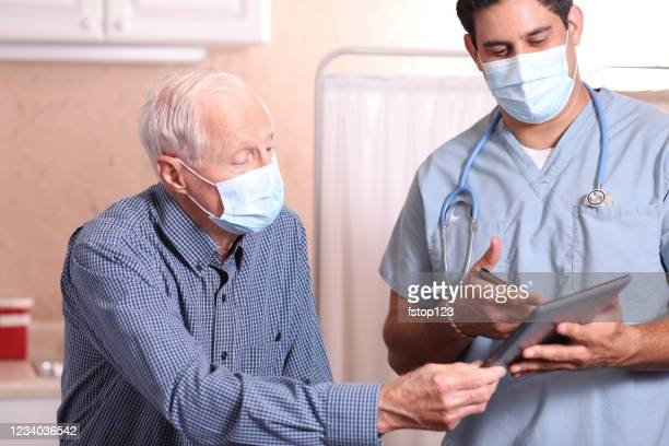 covid-19: latin descent doctor and senior adult patient, masks. - doctor mask stock pictures, royalty-free photos & images