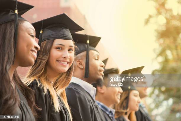 latin descent female college student graduation on campus. - graduation clothing stock pictures, royalty-free photos & images