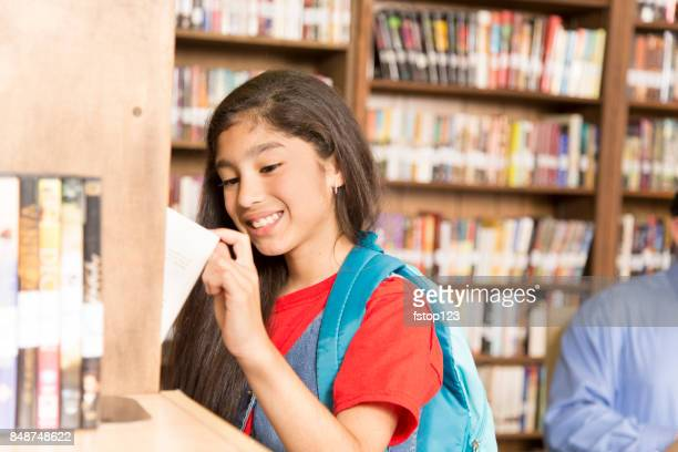 Latin descent girl in school library choosing books.