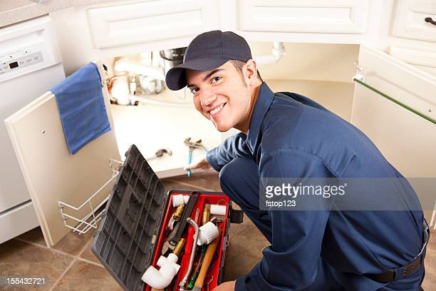 Latin descent plumber, repairman working under sink in home kitchen.