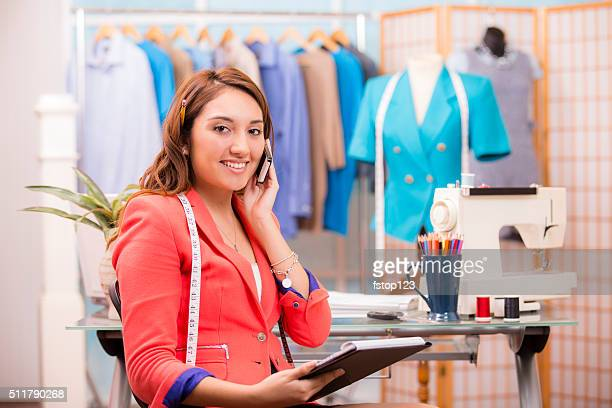 Latin descent, woman business owner. Tailor, boutique. Notepad, phone.