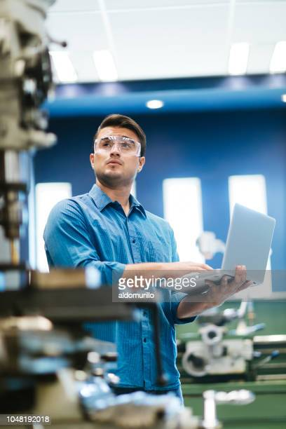Latin engineer working on laptop and drill