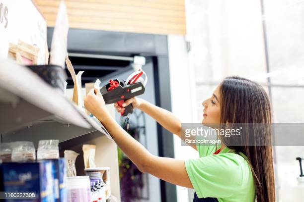 latin ethnic worker of a supermarket labeling the products that are on the shelf. - labeling stock pictures, royalty-free photos & images