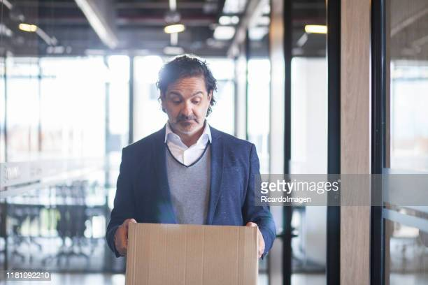 latin executive man looks at the cardboard box he holds in his hands sadly - quitting a job stock pictures, royalty-free photos & images