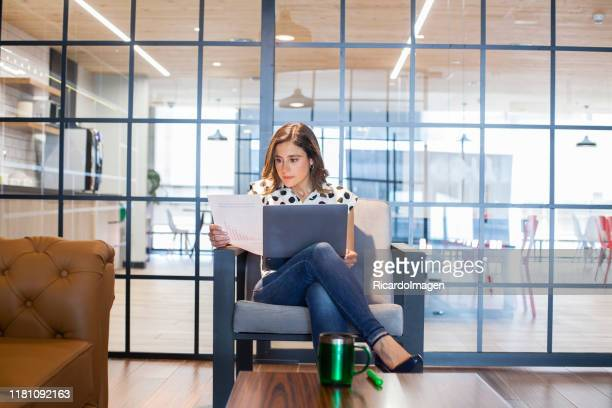 latin executive woman is sitting in office armchair checking documents - bank manager stock pictures, royalty-free photos & images