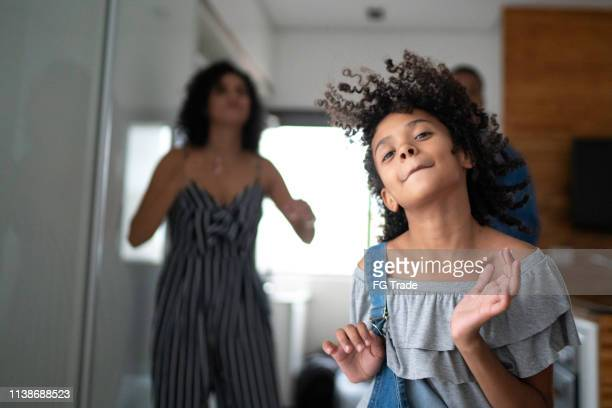 latin family dancing together in the kitchen - family at home stock photos and pictures