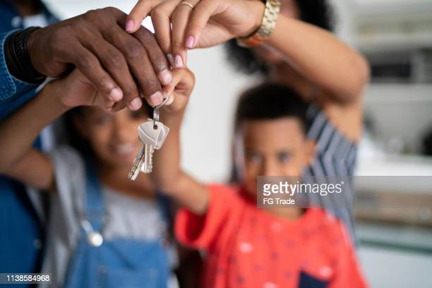 latin family holding the keys of their new house - computer key stock pictures, royalty-free photos & images