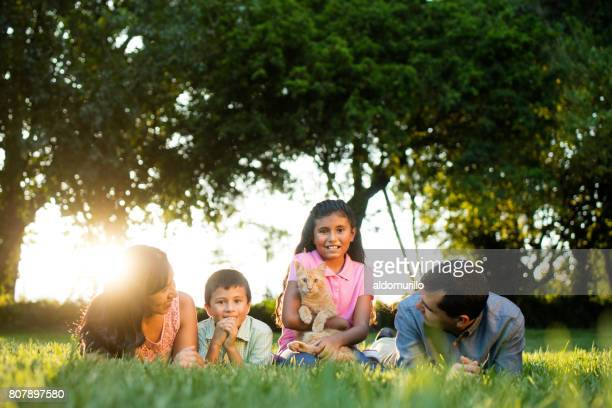 Latin family lying on the grass with a cat