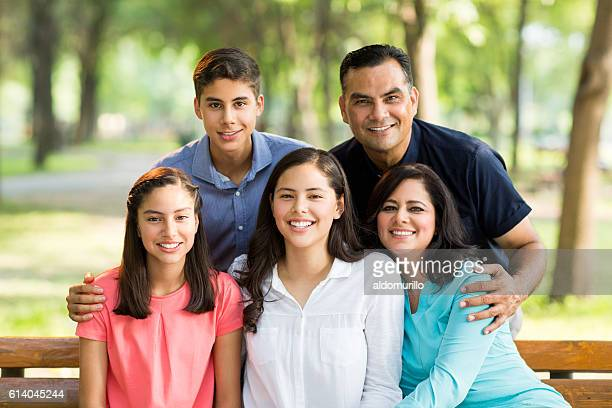 Latin family of five embracing and smiling at camera