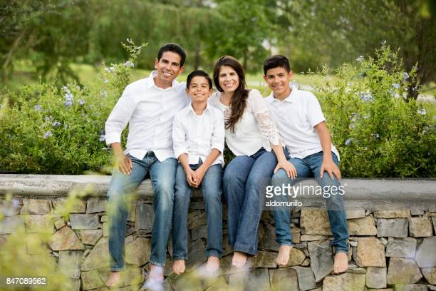 Latin family of four sitting on low wall and smiling