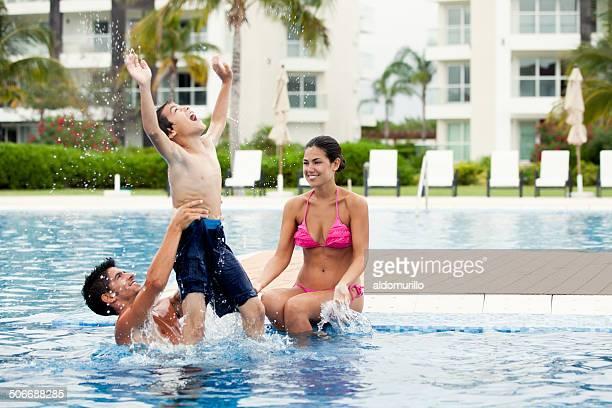 Latin familia jugando en la piscina