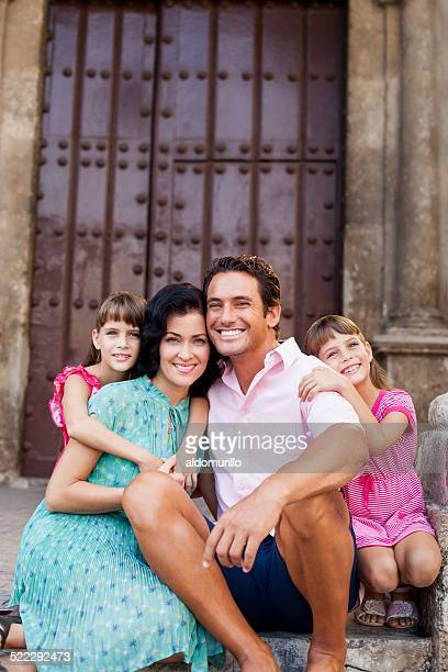 Latin family poses in front of door