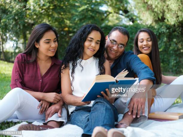 latin family reading together outdoors - mexican picnic stock pictures, royalty-free photos & images
