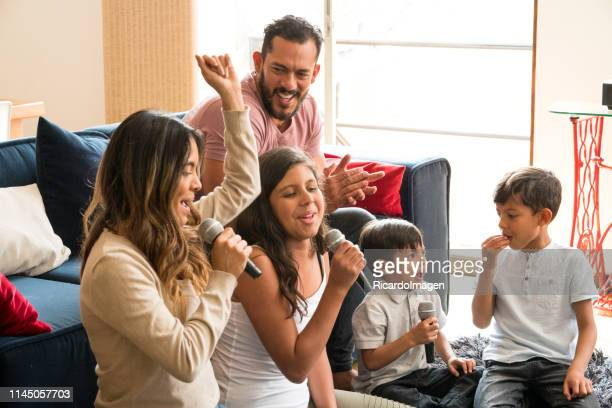 latin family singing karaoke laughing and enjoying all together in the living room of his house - singing stock pictures, royalty-free photos & images