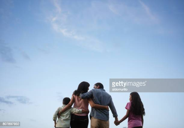 latin family standing together with sky in background - four people stock pictures, royalty-free photos & images