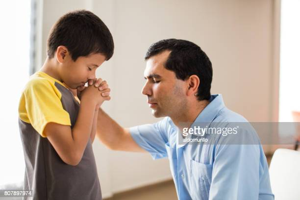 latin father and son praying face to face - praying stock pictures, royalty-free photos & images