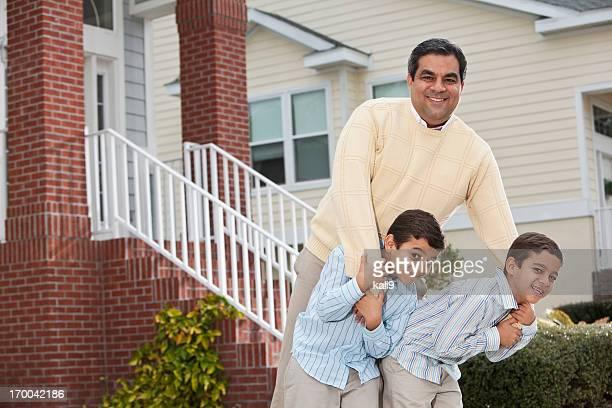 Latino-père et deux garçons à l'extérieur d'une maison individuelle