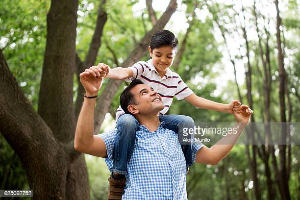 Latin father carrying son on shoulders and looking up