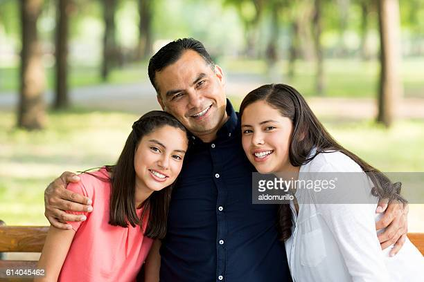 Latin father embracing his daughters and smiling at camera