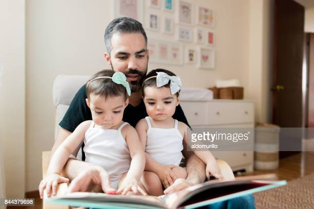 Latin father reading book to baby twins on lap
