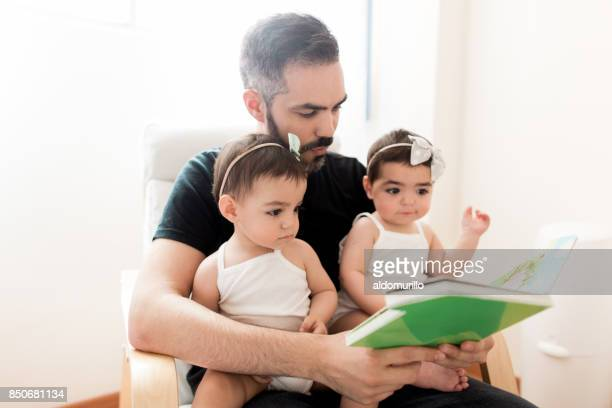 Latin father sitting with babies on lap and reading book